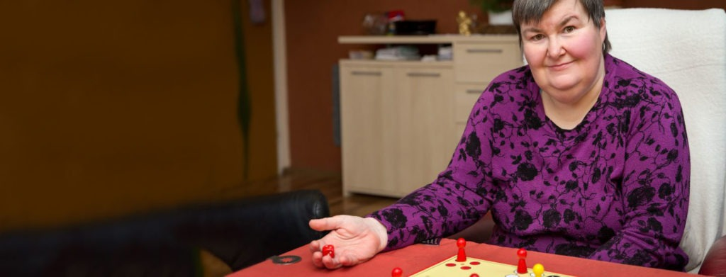 A woman with disabilities playing a game at the table